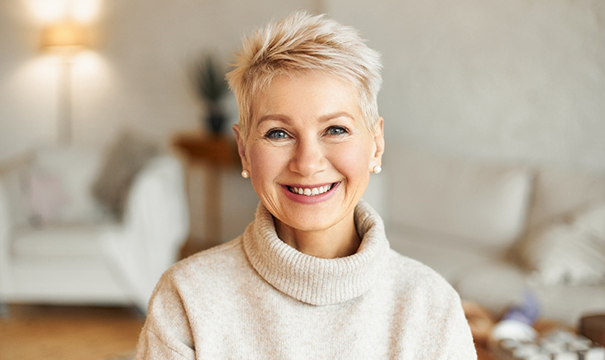 An older woman wearing a sweater and smiling, showing off her restored smile because of dental crowns