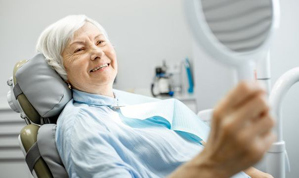 older woman admiring her smile with dentures in Newton