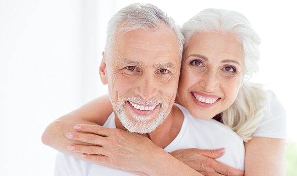 Older couple with implant-retained dentures in Newton smiling