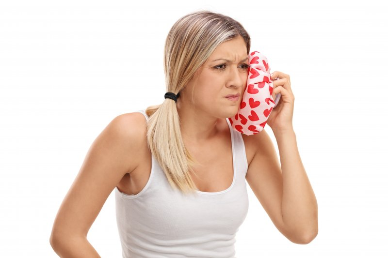 woman holding ice pack to her jaw