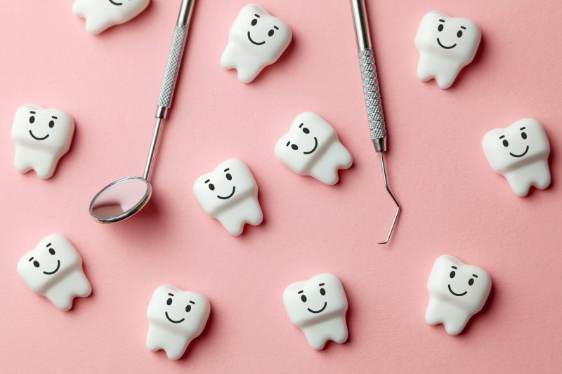 Cartoon smiling molars lying next to dental tools